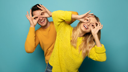 Sweet and crazy couple. A cheerful couple in yellow sweaters are goofing around together, making...