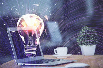 Obraz Computer on desktop in office with bulb icon hologram. Multi exposure. Concept of idea. - fototapety do salonu