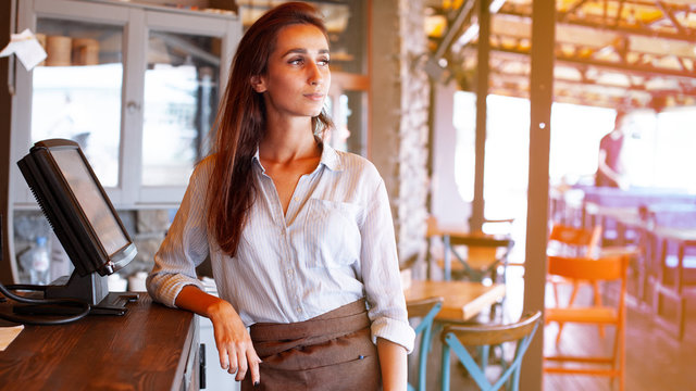Waist portrait of waitress registrated orders to the payment terminal. Young and beautiful waitress stand near sale terminal and check the order.
