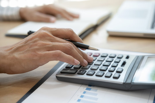 Close-up of business woman hand using calculator to calculate business data, accountancy document at home office.