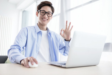 Portrait of a smiling young man in plaid shirt sitting on a floor with laptop computer and showing ok gesture isolated over white background