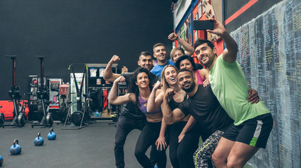 Group of multiracial athletes taking a selfie with the mobile in the gym