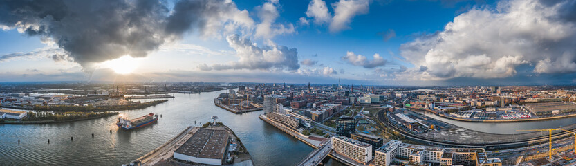 Aerial drone panoramic view of port of Hamburg from above before sunset with dramatic stormy clouds over the sea port
