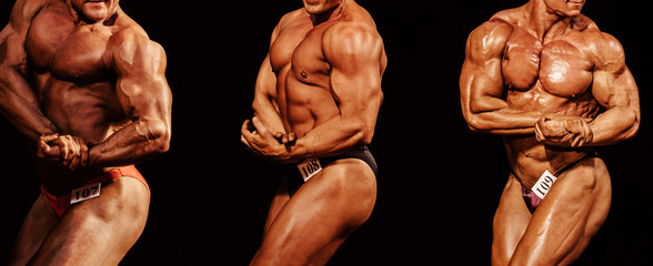 group athletes bodybuilders posing biceps on hand in bodybuilding competition on black background