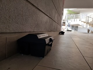 Pest control rat trap which contains poison placed at shady area at a office building