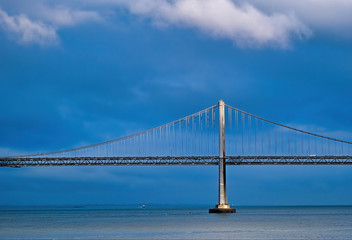 Fotomurales - Sunlight on Bay Bridge Through Storm Clouds