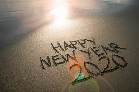 Happy New Year 2020 message handwritten in clean sand under glowing lens flare sunrise on an empty beach