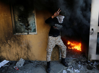 A member of Hashd al-Shaabi (paramilitary forces) flashes the victory sign as he stands next to a reception room of the U.S. Embassy with fire, during a protest to condemn air strikes on bases belonging to Hashd al-Shaabi (paramilitary forces), in Baghdad