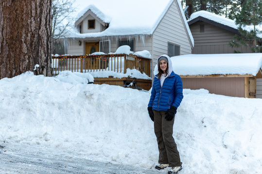 Pretty local mountain community teenager girl dressed warm in front of plowed snow bank in her Wrightwood neighborhood home.