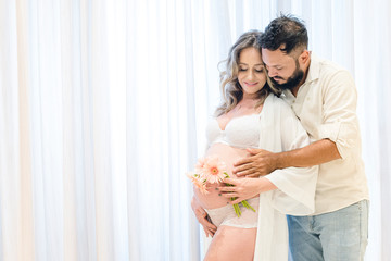 Handsome Latin man and his beautiful pregnant wife, Couple holding each other holding flower. Curtain background. pregnancy concept. Wall mural
