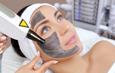 Cosmetologist does Carbon face peeling procedure of a beautiful, young woman in a beauty salon. Hardware cosmetology treatment and Spa.