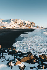 Well known Black Sand Beach in town of Vik in Iceland during the winter sunset time. Beautiful Icelandic scenery, Tourism, dramatic landscape