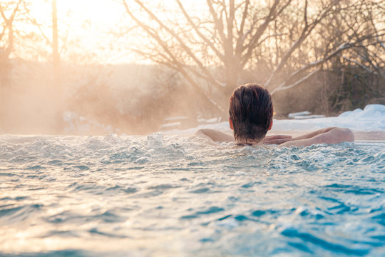 outdoor swimming pool in winter with relaxing young woman