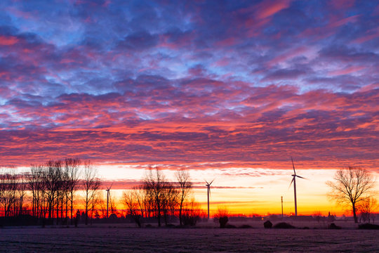 sunrise with windmills and colourfull clouds