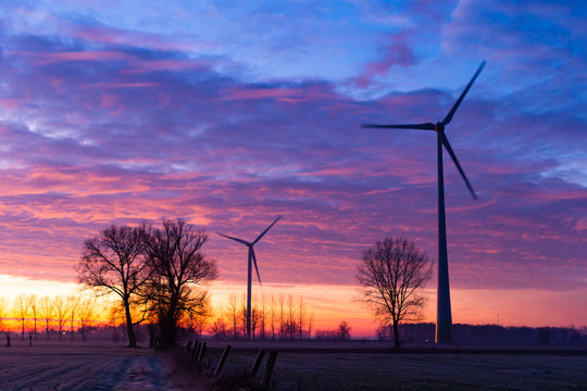 2 windmills in front of colourfull clouds