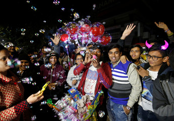People gather around a vendor blowing bubbles during celebrations to welcome the New Year in a road in Ahmedabad