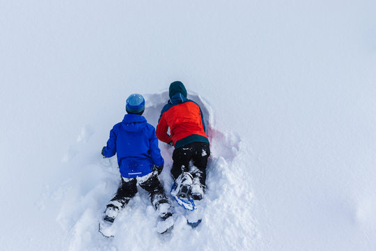 Youths Digging in a Snowbank during Winter