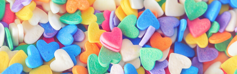 Heap of colorful candies confetti heart shape. Valentine Day holiday concept. Toned with retro vintage filters. Web banner header for website. Pink small lonely heart among many others.
