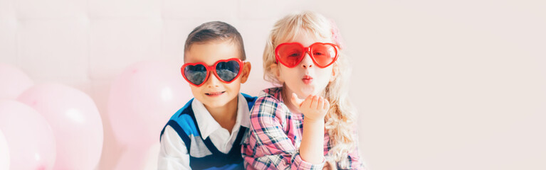 Valentine day holiday celebration. Web header banner for website. Two happy Caucasian cute funny children kids wearing heart shape glasses. Boy and girl hugging. Love, friendship and fun.
