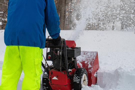 Man pushing snowblower during snowstorm