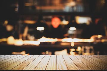 Empty wooden table with blurred restaurant kitchen background.