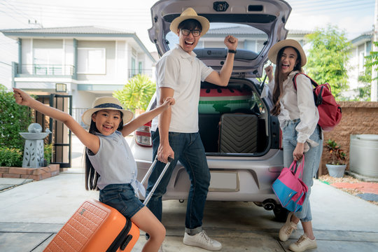 Portrait of Asian family with father, mother and daughter looks happy while preparing suitcase into a car for holiday. Shot in the house garage..