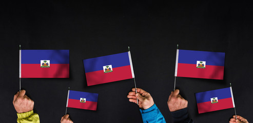 Hands holds flags of Haiti  on dark background