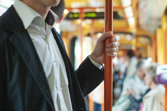 passenger commuter in public transport, commuting people in bus or tram, close up of hand holding handrail bar