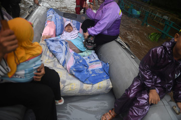 An elderly woman is being evacuated on an inflatable boat by a rescue team, after floods hit a residential area in Depok, south of Jakarta