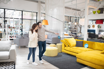 Two people discussing furniture models in a modern furniture shop