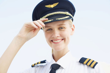 portrait of professional female pilot smiling wearing uniform. Young woman happy at work  Wall mural