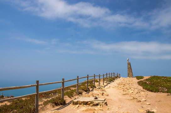 Portugal, Cabo da Roca, The Western Cape Roca of Europe,  hiking trails on the Cape Roca,  wooden handrails at the  stone road, a cross on the top of the monument at Cabo da Roca