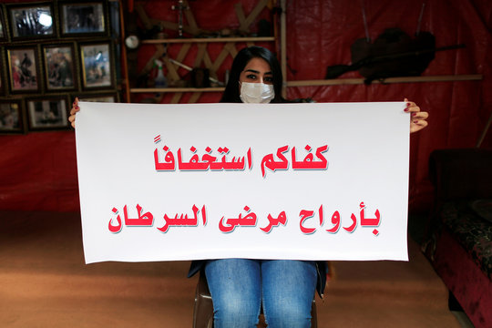 """An Iraqi young woman who is affected with cancer holds a banner that reads """"Enough underestimate to the lives of cancer patients"""" during ongoing anti-government protests, at Tahrir Square in Baghdad"""