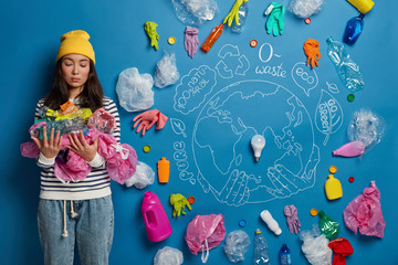 Aluminium Prints Submarine Horizontal shot of serious Asian woman carries plastic garbage, wears yellow hat and striped jumper, collects wastes everywhere, poses against blue background, drawn planet. Ecology concept.