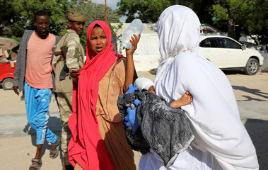 A woman reacts as an injured child is assisted at the Madina hospital, following a car bomb explosion at a checkpoint in Mogadishu