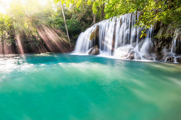 Waterfall and blue emerald water color in Erawan national park with sun light and light ray...