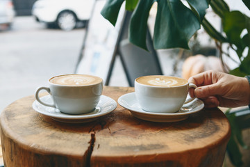 Two cups of aromatic coffee cappuccino or latte on a wooden table. person holds a cup with hand....