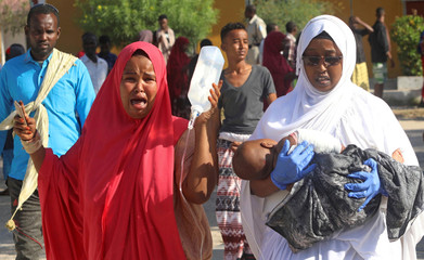 A woman reacts as an injured child is assisted at the Madina hospital following a car bomb explosion at a checkpoint in Mogadishu