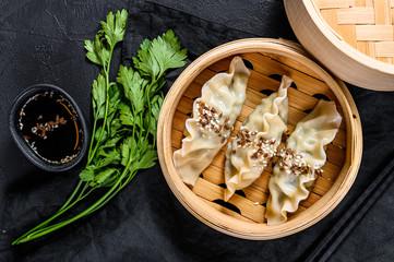 Foto auf AluDibond Shanghai Korean dumplings in a traditional bamboo steamer. Top view. Rustic old vintage black background