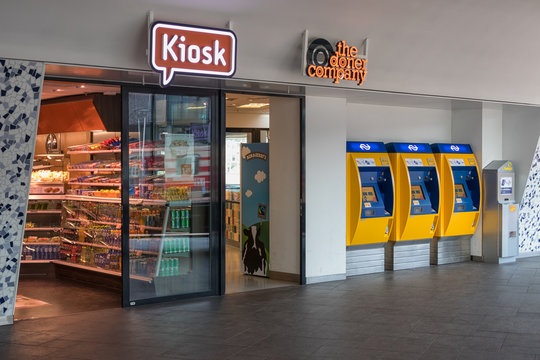 Kiosk and three yellow ticket machines at Dutch railway station