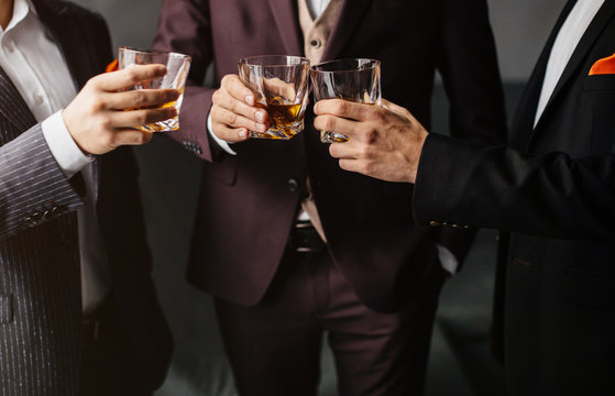 Close-up partial view of three friends clink glasses of whiskey drink, alcoholic beverage. Men in formal wear toasting with glasses of whiskey. Whisky drink