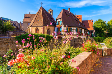 Beautiful traditional colorful houses decorated with flowers in picturesque Kaysersberg village,...