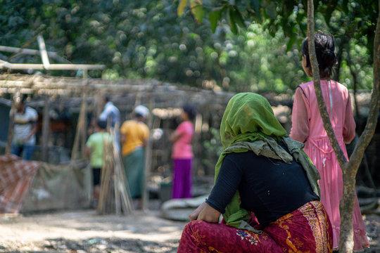 rohingya refugee woman sitting under a tree in refugee camp in teknaf bangladesh