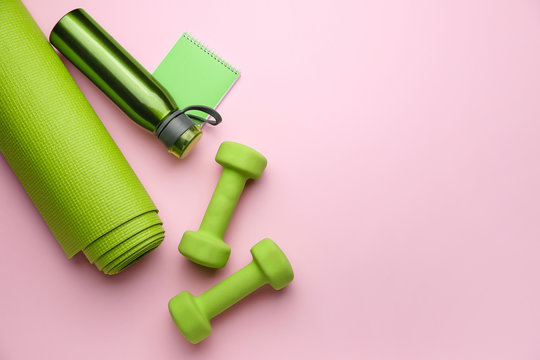 Dumbbells with notebook, yoga mat and bottle of water on color background