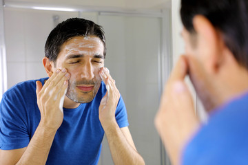 Man washing face with facial cleanser face wash soap in bathroom at home. Men skin care concept.