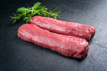 Raw dry aged venison tenderloin fillet steak natural with herbs offered as closeup on a modern...