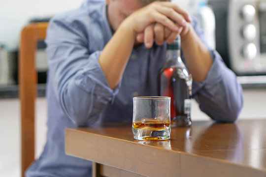 A man with bottle of whiskey on the kitchen. The concept of drunkenness and alcoholism. Alcoholic father.