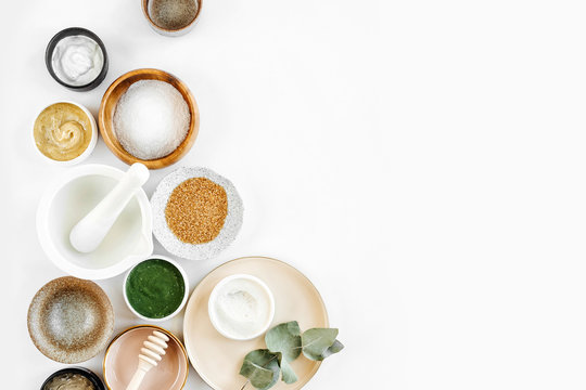 Beauty treatment ingredients for making homemade skin care cosmetic mask. Various bowl with clay, cream, essential oil and natural ingredients  on white table background. Organic spa cosmetic products