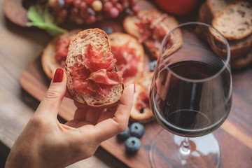 Foto auf Leinwand Wein Selective foucs on finger holding ham jamon serrano and glasses of red wine on wooden board