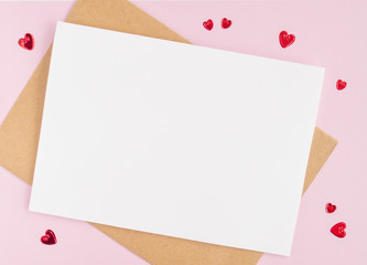 Minimalistic card mockup with envelope, postcard, pen, red hearts on  pink background. Flat lay, top view, copy space. Valentines day concept.